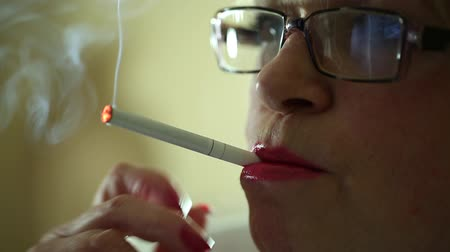 carcinogenic : Senior woman with glasses smoking a cigarette. Female smoker, close up shot