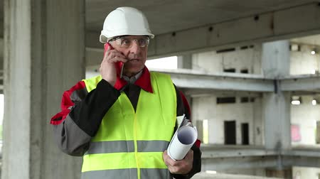 site : Civil engineer with red cell phone at suspended construction project. Builder in white hard hat with red smartphone and building drawing at project site