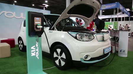 electromotor : UKRAINE, KIEV, JUNE 10, 2016: People at exhibition of electric cars. White KIA Soul EV electromobile is being charged. Car with openned bonnet