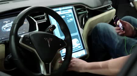motorcar : UKRAINE, KIEV, JUNE 10, 2016: People at exhibition of electric cars. Man with smartphone inside Tesla electromobile at exhibition of electric cars Stock Footage