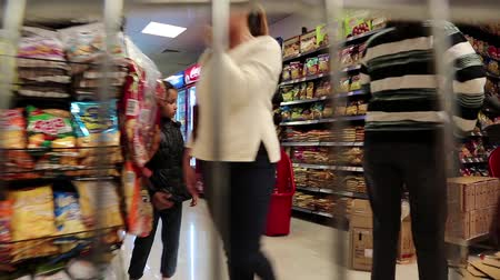 посылка : UAE, DUBAI, FEBRUARY 3, 2016: People and counters with goods inside supermarket in Dubai, United Arab Emirates. View from the moving shopping trolley