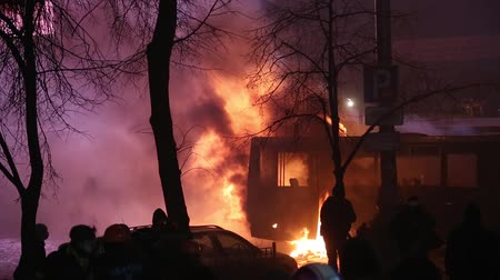 protesto : UKRAINE, KIEV, JANUARY 19, 2014: Thousands of anti-government protesters clashed with riot police, burning police buses and attacking with stones, sticks and fires after tough laws were passed.