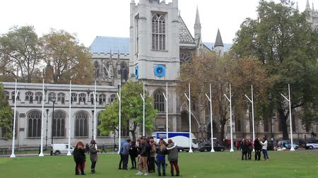 popularly : LONDON, UK, MART 24, 2013: People near Westminster Abbey in London, England. The Collegiate Church of St Peter at Westminster, popularly known as Westminster Abbey, is a large, mainly Gothic church, in the City of Westminster, London, located just to the