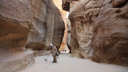 besom : JORDAN, PETRA, DECEMBER 5, 2016: Cleaner in Siq - a narrow passage, gorge that leads to the ancient city of Petra, originally known to Nabataeans as Raqmu - historical and archaeological city in Jordan