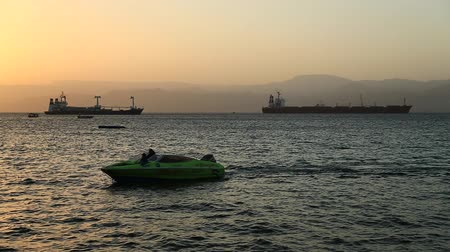 JORDAN, AQABA, DECEMBER 10, 2016: Motor boats in sea near Aqaba city, Hashemite Kingdom of Jordan. Red Sea, Gulf of Aqaba. Silhouettes of ships in the sea at sunset