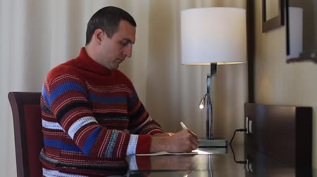 üzenetküldés : Man sits at the table and writes a letter. Man in sweater sits on a chair at the table and writes on white paper