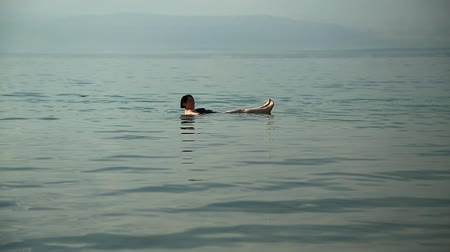 JORDAN, DEAD SEA, DECEMBER 8, 2016: Woman swim and relax in the salty water of the Dead Sea, Hashemite Kingdom of Jordan. People swim in Dead Sea