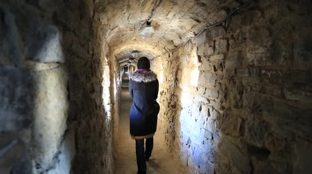Woman goes inside stone fortress, Kamianets-Podilskyi city, western Ukraine Стоковые видеозаписи