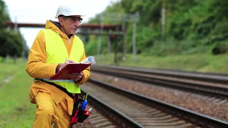 railwayman : Railway worker in uniform. Inspector of railway traffic. Railway worker in yellow uniform on railway line Stock Footage