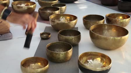curar : Bronze Tibetan singing bowls in the meditation hall. Yellow Tibetian bowls Stock Footage