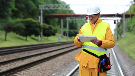 railwayman : Railway worker in yellow uniform with tablet computer stands on railway line. Railway worker makes notes in his tablet computer. Railway worker in uniform and white hard hat with tablet pc in hands