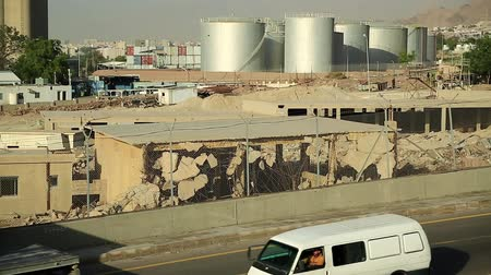 depositary : JORDAN, AQABA, DECEMBER 10, 2016: Container truck rides near industrial area with large capacity tanks close to Aqaba city, Hashemite Kingdom of Jordan