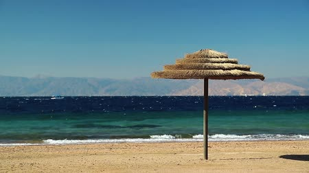 aqaba : Tropical resort in Tala Bay, Hashemite Kingdom of Jordan. Red sea, gulf of Aqaba. Umbrella on the beautiful beach. View on Israel and Egypt on the other coast Stock Footage