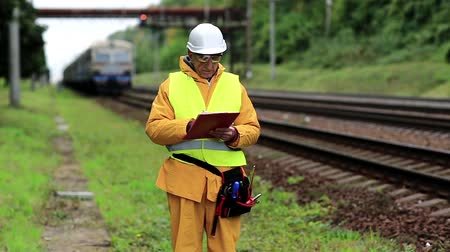 railwayman : Railway worker in uniform with documents. Inspector of railway traffic. Railway worker in yellow uniform on railway line Stock Footage