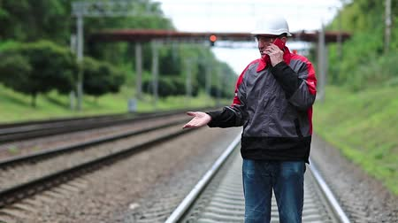 railwayman : Railway worker with smartphone in hand. Railway worker in uniform on railway line talks on mobile phone. Manager of works in white hard hat. Phone upside down in the hand Stock Footage