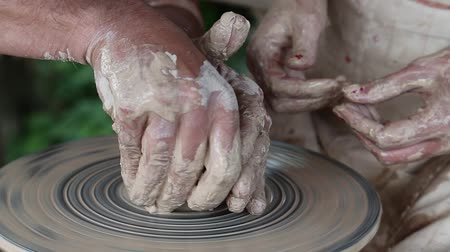 Hands of a potter and his apprentice. Man and woman makes a pot on a pottery wheel. Woman is the pupil of a potter. Man and woman hands