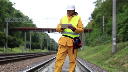 railwayman : Railway worker in yellow uniform on railway line with tablet. Inspector of railway traffic. Railway worker with tablet computer