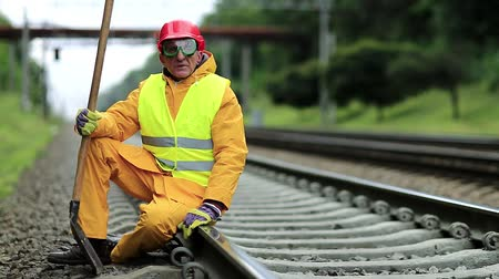 railwayman : Railwayman in yellow uniform with shovel in hand. Railway construction. Railway worker in red hard hat sits on rail and looks at the camera. Workman with spade on railway track