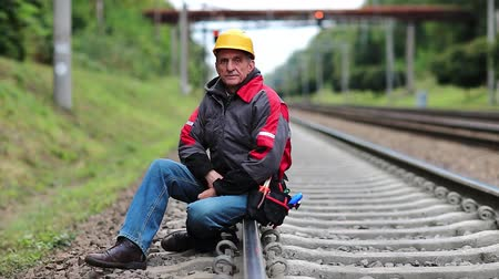 railwayman : Railwayman in yellow hard hat sits on rail and looks at the camera. Workman on railway track. Railway worker sits on railway line