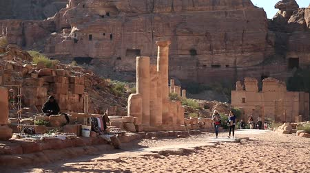 JORDAN, PETRA, DECEMBER 12, 2016: People on the Colonnade Street in Petra - the ancient city in Hashemite Kingdom of Jordan. Temenos Gate and Temple of the Qasr al-Bint at the distance