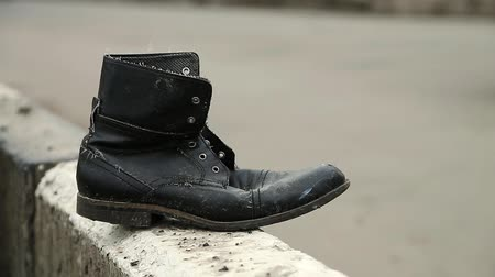 Boot near the highway, traffic violation and road accident. Old black shoe near the road. Jaywalking, do not run across road Стоковые видеозаписи