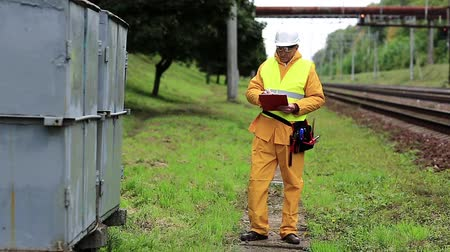 railwayman : Electrician makes notes in his documents. Railway employee in yellow uniform on railway line. Railway worker in yellow uniform and white hard hat with documents in hands Stock Footage