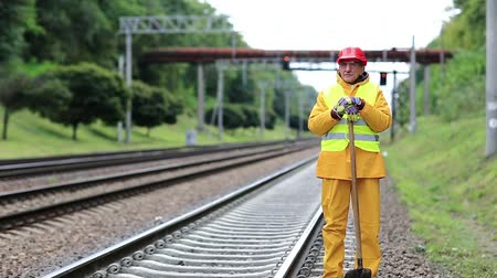 Workman with shovel on railway track. Railwayman with shovel in hands on railway track. Repairman worker in yellow uniform with shovel in hands mends railway line Stock Footage