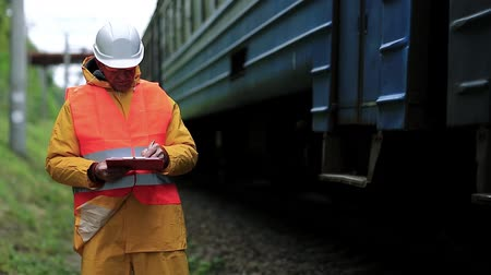 railwayman : Inspector of railway traffic. Railway worker in uniform with documents. Railway worker in yellow uniform on railway line Stock Footage
