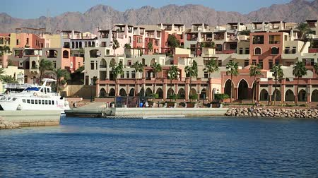 aqaba : JORDAN, AQABA, DECEMBER 10, 2016: People on embankment in harbor in Tala Bay resort near Aqaba city, Hashemite Kingdom of Jordan Stock Footage