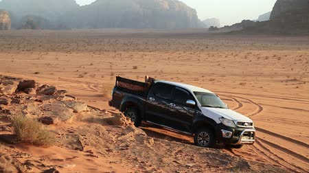 JORDAN, WADI RUM DESERT, DECEMBER 6, 2016: Off-road car in Wadi Rum desert, Hashemite Kingdom of Jordan. Wadi Rum, also known as Valley of the Moon. Wadi is a term traditionally referring to a valley Stock Footage
