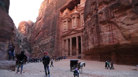JORDAN, PETRA, DECEMBER 5, 2016: Horse and people near Al Khazneh or the Treasury at Petra, originally known to Nabataeans as Raqmu - historical and archaeological city in Hashemite Kingdom of Jordan Стоковые видеозаписи