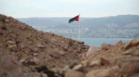 aqaba : Flag of the Arab Revolt in Aqaba city, Hashemite Kingdom of Jordan, Red Sea, gulf of Aqaba and Eilat city in Israel at the distance. Two country in one video clip