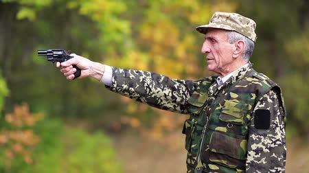 harcias : Man with black gun. Senior man in military uniform shoots a revolver. Retired officer at shooting range. Senior man in the military uniform shoots a pistol in forest Stock mozgókép