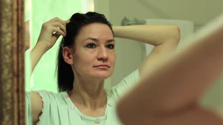 oneself : A woman looks into the mirror and makes a hairdo. Adult woman picks her hair in front of the mirror. Woman looks into the mirror in the bathroom and pretothes her Stock Footage