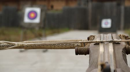 harcias : Old wooden arbalest and targets at background. Crossbow is aimed at a target. Ancient ballista Stock mozgókép