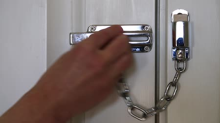 защелка : Woman closes the door with the safety chain. Hand and door safety chain