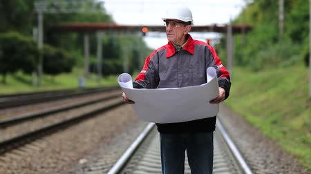 railwayman : Railwayman in white hard hat with work scheme in hands. Railway worker with design drawings in hands stands on rail branch