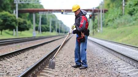 railwayman : Workman with shovel on railway track. Repairman worker with shovel in hands mends railway line. Railwayman in uniform with shovel in hands. Back hurts, low back pain, lumbago Stock Footage