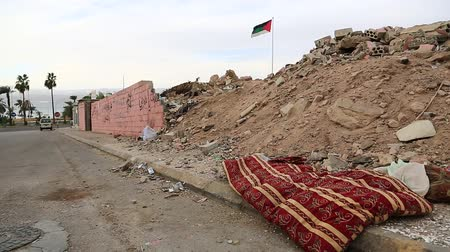 aqaba : Red mattress lies on the road. Garbage lies on the street in Aqaba, Jordan. National flag of Jordan on the background Stock Footage