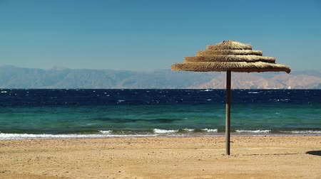 aqaba : Red sea, gulf of Aqaba, umbrella on the beautiful beach. Tropical resort in Tala Bay, Hashemite Kingdom of Jordan. View on Israel and Egypt on the other coast