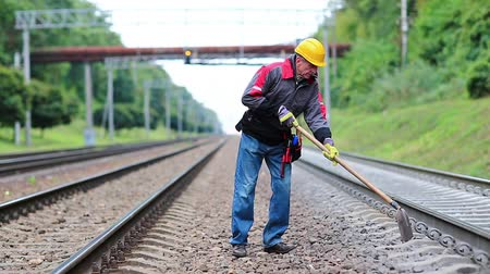 railwayman : Repairman worker with shovel in hands mends railway line. Workman with shovel on railway track. Railwayman in uniform with shovel in hands
