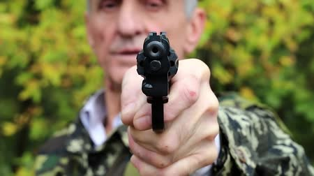 harcias : Man holds in hand black revolver and looks at the camera. Retired officer in the military uniform at shooting range Stock mozgókép