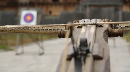 harcias : Old wooden arbalest and targets at background. Ancient ballista. Crossbow is aimed at a target
