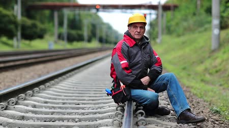 slogger : Railwayman in yellow hard hat sits on rail and looks at the camera. Workman on railway track. Railway worker sits on railway line