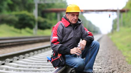 railwayman : Railway worker sits on the railway line. Workman on railway track. Railway worker sits on railway line Stock Footage
