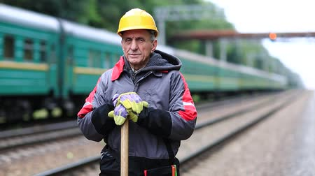 railwayman : Railway man in hard hat with shovel in hands. Railway worker in uniform with shovel stands on railway line. Workman on railway track. Clip with vibration from away train Stock Footage