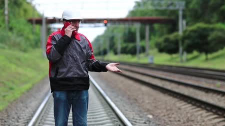 hat : Railway worker with smartphone in hand. Railway worker in uniform on railway line talks on mobile phone. Manager of the works in hard hat. Phone upside down in the hand