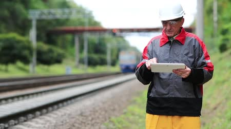 railwayman : Railway worker with tablet computer on railway line. Inspector of railway traffic. Railway worker with tablet pc in looks at the train