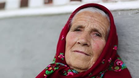 starość : Senior woman looks at the camera and smiles. Elderly woman in red headscarf sits near gray wall of his house and looks at the camera. Looks at the camera and smiles, wrinkled face