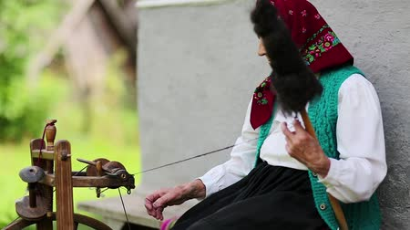 starość : Elderly woman sits on bench and works with distaff with spinning wheel. Ukrainian old woman sits on a bench near his house and spin yarn. Female with spinning wheel, handicraft
